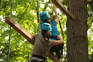 2 campers climb on high ropes