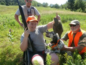 Camper in wheelchair holds up grouse he just shot while instructors and dog look on