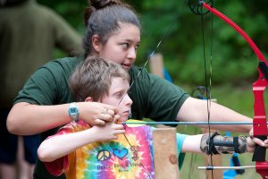 camp counselor helps camper learn to shoot a bow