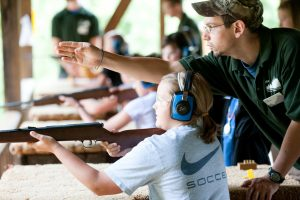 Camper getting instruction from counselor at shooting range