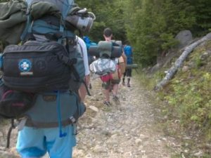 Extreme survivor campers hiking with their packs