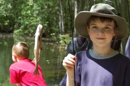 Camper holding a fishing rod with fish at the pond