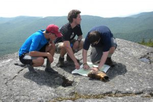 3 campers consult a map on a mountain top