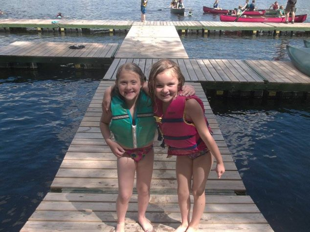 Two young campers on the dock with canoes in background