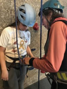 adult volunteer helps youth at climbing wall