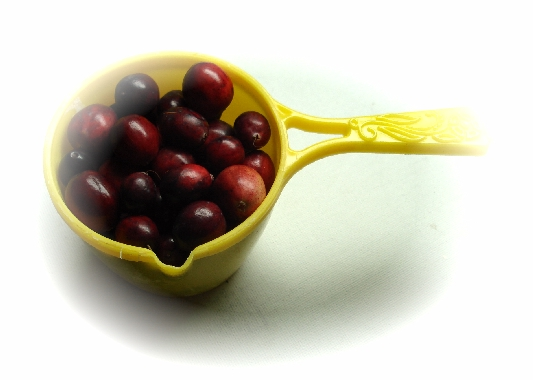 A yellow measuring cup full of ripe Maine cranberries