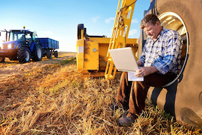A farmer sitting in a tractor tire and working on a laptop.