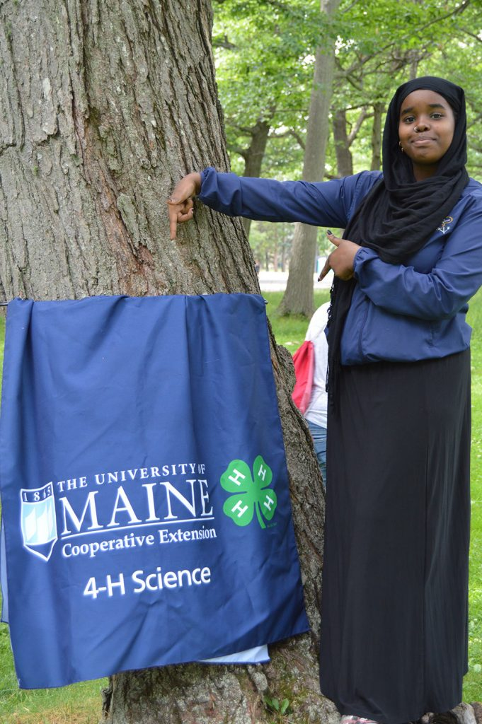 teen at 4H summer of science with a banner from the event