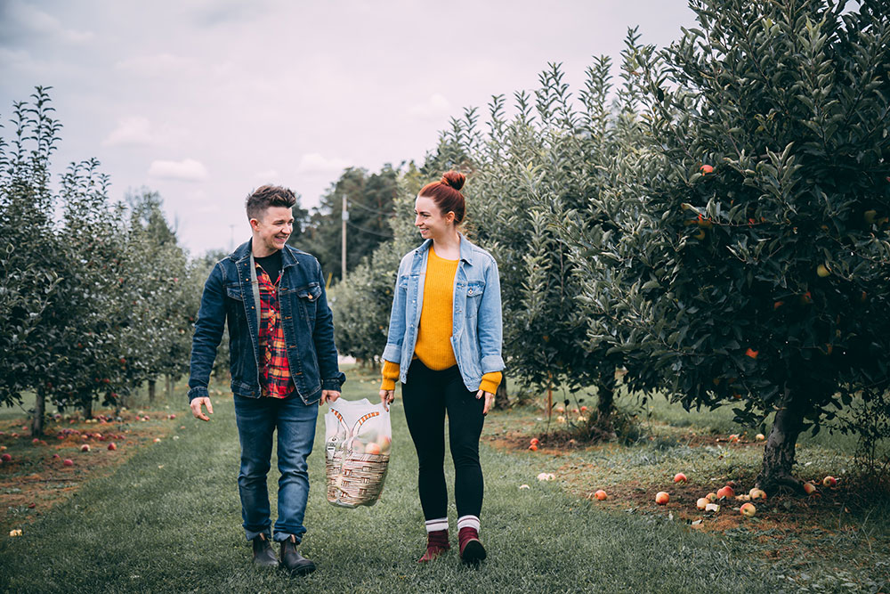 Young couple with a bushel of apples in an apple orchard