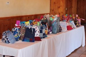 Table covered with bags filled with items for those in need.