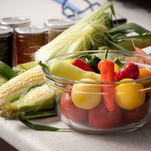 fresh corn on the cob, chili peppers, tomatoes, and canning jars containing canned produce