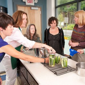 Participants make pickles in a food preservation class