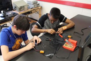 two teenagers building electronics at a table