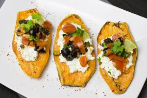 Baked Sweet Potato Boats on a plate with sour cream, peppers, olives, and garnish.