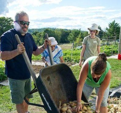 Man with wheelbarrow, gardeners watching