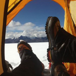 View of researchers' feet as they rest in their tent and look out across the ice sheet at the mountain range beyond