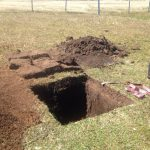 Bleaker Test Pit: sod and soil piled next to a square hole. A shovel and tape measure lay nearby.