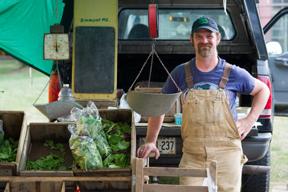 Farmer selling fresh produce at a farmers market; photo by Edwin Remsberg, USDA