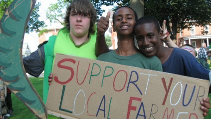"""3 youths hold a sign that says """"Support Your Local Farmer"""""""