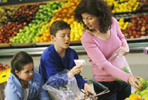 mother and 2 kids grocery shopping