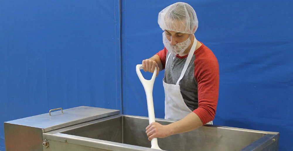 cheesemaker demonstrating good personal hygiene by wearing clean clothes put on just for cheesemaking and wearing hair and beard protection