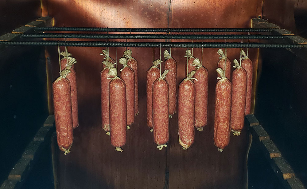 sausages hanging up in a smoker