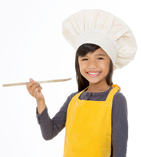 girl with spoon wearing a chef's hat