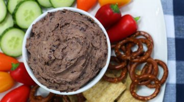 Picture of Black Bean Hummus served on a plate with veggies, pretzels, and crackers