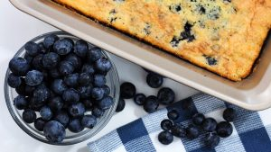 Blueberry cobbler with dish of fresh blueberries