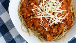 Picture of Lentil Spaghetti Sauce on top of whole wheat spaghetti in a white bowl