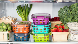 Storage containers in a refrigerator with fresh produce on the shelves