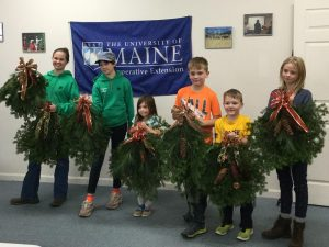 youth displaying the fir wreaths made at the money can grow on trees workshop