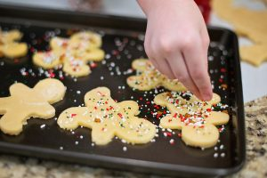 child decorates cookies before baking