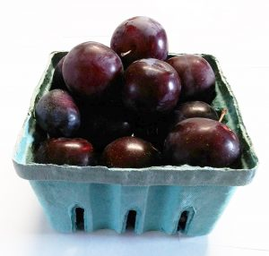 Quart-sized container filled with plums