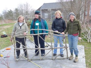 Brae Maple volunteer Linda Redmond (left) teaches new master gardeners how to build fences from twigs and saplings.