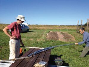 Biddeford Farmer, Brent Peters, and York County Master Gardener Volunteer, Allan Amioka, use hoop bender for a greenhouse frame.