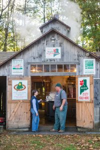 Maine maple syrup producer talks with Extension educator outside his sugar shack