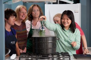 Master Food preserver lifts a canning jar from a hot water bath while demonstration participants look on