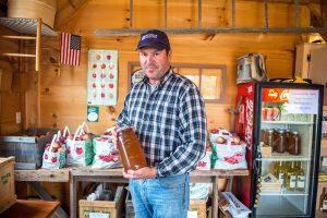 Apple grower holding bottled cider in his shop