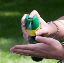 Woman sprays insect repellent into her hand