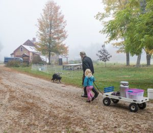 Goat farmer and child pulling a wagon toward the barn