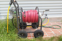 """This hose cart provides storage for the hose and fittings that supply water to a drip irrigation system when they are not in use. The """"Y"""" fitting at the spigot provides a way to drain water from the main hose."""