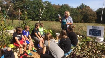 Woman teaching children about gardening