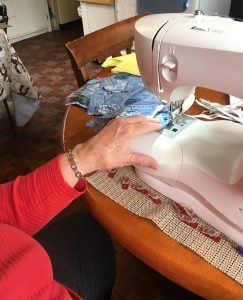 a senior woman getting ready to sew a protective mask