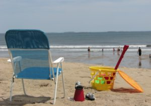 Beach chair and kid's toys on sandy beach