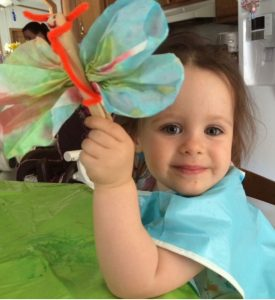 Child holding up tissue-paper butterfly