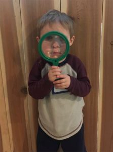 child with magnifying lens
