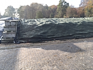 Bunker silo on cobblestone with plastic covered with a tarp and sandbags on edges.