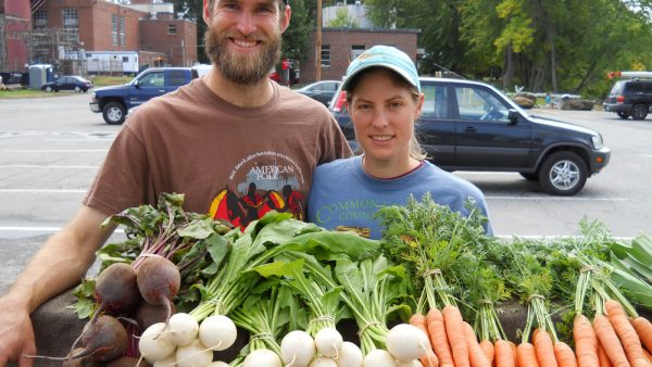 farming couple with produce at farmers market