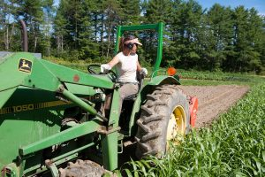 woman farmer on tractor plowing field